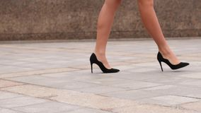 woman legs in black high heels shoes walking in the city urban street. Steadicam Stabilized shot, Female legs in