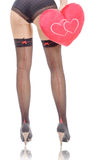 Sexy woman legs in black stocking with plush heart. A sexy woman legs in black stocking with plush heart Royalty Free Stock Photos
