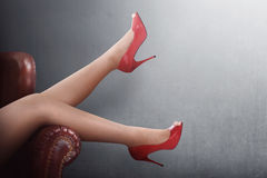 Sexy woman legs in red high heels on a couch Stock Images