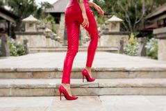 Sexy woman legs in red pants and high heels. Sexy woman legs in red pants and red high heels Royalty Free Stock Photography