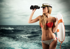 Woman lifeguard. Woman with lifesaver looking out to sea with binoculars royalty free stock photos