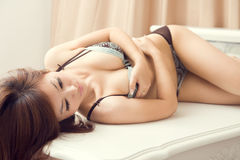 Sexy woman in lingerie lying on table Stock Photos