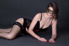 Sexy woman in lingerie and mask lying over grey Royalty Free Stock Photo