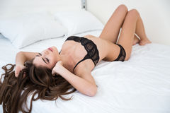 Sexy woman in lingerie relaxing on the bed. Portrait of a sexy woman in lingerie relaxing on the bed at home Stock Photo