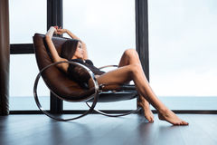 Sexy woman in lingerie relaxing on rocking chair Royalty Free Stock Image