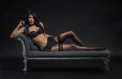 Sexy woman in lingerie sitting on couch Stock Images