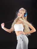 Sexy woman listening for the music using headphones Stock Images