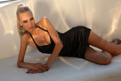 Sexy woman with long blond hair wearing elegant black dress Stock Photo