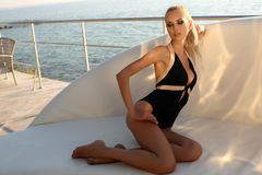 Sexy woman with long blond hair wearing elegant black swimsuit Royalty Free Stock Image