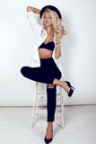 Sexy woman with long blond hair wears elegant black costume, hat, shoes Royalty Free Stock Photo
