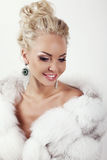 Sexy woman with long blond hair wears luxurios fur coat and bijou. Fashion studio photo of gorgeous sexy woman with long blond hair wears luxurios fur coat and Royalty Free Stock Photo