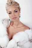 Sexy woman with long blond hair wears luxurios fur coat and bijou. Fashion studio photo of gorgeous sexy woman with long blond hair wears luxurios fur coat and Royalty Free Stock Photos