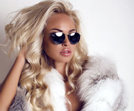 Sexy woman with long blond hair wears luxurios fur coat and sunglasses. Fashion studio photo of gorgeous sexy woman with long blond hair wears luxurios fur coat Royalty Free Stock Photos