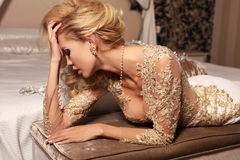 Sexy woman with long blond hair wears luxurios lace wedding dress and bijou. Fashion interior photo of gorlgeous sexy woman with long blond hair wears luxurios Stock Photo
