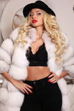 Sexy woman with long blond hair wears luxurious white fur coat Royalty Free Stock Photography
