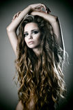 Woman with long curly hair. Studio portrait of a beautiful woman with gorgeous long hair stock image
