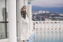 Woman with long hair in amazing clothes. Beautiful woman in amazing clothes posing in hotel stock image