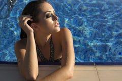 Sexy woman with long hair in bikini relaxing in swimming pool Royalty Free Stock Photo