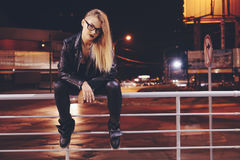 Woman with long hair in leather clothes on night city lights background. Portrait of young woman with long hair in leather clothes on night city lights stock photos