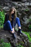 woman with long hair at stone. girl in casual clothes outdoor. look of girl near stony wall. Summer or spring royalty free stock photos