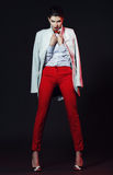 Sexy woman with long legs in red pants. And white coat Royalty Free Stock Photos