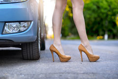 Sexy woman with long legs standing near the car on the road Royalty Free Stock Photos