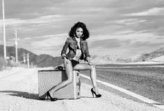 Sexy woman long legs suitcase open road. Beautiful young sexy exotic woman long legs sitting on luggage suitcase wearing bikini and denim jacket on a lonely Stock Photo