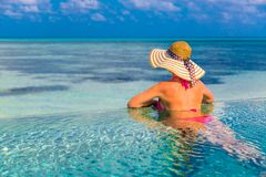 Sexy woman in the pool on the beach with a pink bikini and hat watching the endless sea. Sexy woman looking at the blue sea from infinity pool Royalty Free Stock Photo