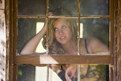 A sexy woman looks outside through a window Royalty Free Stock Image