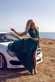 Sexy woman in luxurious dress posing beside a white car Royalty Free Stock Image