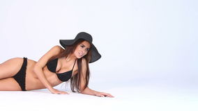 woman lying in black bikini and hat on white stock video footage