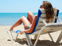 Sexy woman is lying on chair at a beach. Sexy woman is lying on chaise longue near a sea, view from behind Royalty Free Stock Photos
