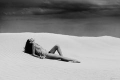 Sexy woman lying in desert Royalty Free Stock Images