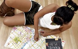 Sexy woman lying on the floor reads travel map Royalty Free Stock Images