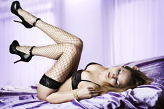 Sexy woman lying on silk violet bed Stock Image