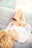 Sexy woman lying on sofa and using smart phone Stock Photo