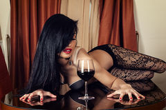 Sexy woman lying on a table with a wine glass Royalty Free Stock Images
