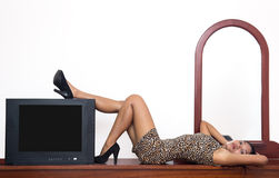 Sexy woman lying on wooden table. Attractive Asian woman with a television Royalty Free Stock Photo