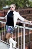 The woman in a miniskirt, on the bridge, against railway ca Stock Photo