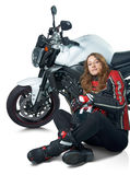 Sexy woman at motorcycle. Young sexy woman in a leather suit sitting at white motorcycle and holding a helmet Royalty Free Stock Images
