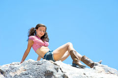 Sexy woman on mountaintop. A sexy woman with short shorts and piggy tails sits on a mountaintop Stock Photography