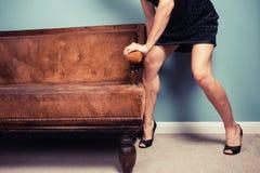 Sexy woman moving sofa Stock Image