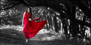 Sexy woman with naked breast in red dress in fairy forest. Sexy fashion model with naked walking in a fantastical forest. Photo of seductive nude woman in full Royalty Free Stock Photo