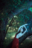 Sexy woman with naked breast in red dress in fairy forest. Royalty Free Stock Photography