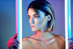 Woman in neon light in lingerie. Neon lights and glare of light on the girls face. Naked woman in sequins on the background. Of bright contrast light. Blonde royalty free stock photos