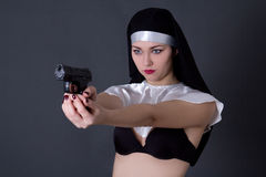 Sexy woman nun in lingerie aiming with gun over grey Stock Photo