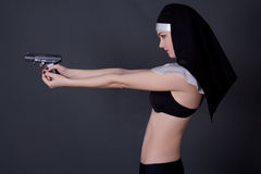 Sexy woman nun in lingerie shooting with gun over grey Royalty Free Stock Images