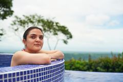 Woman in outdoor pool. Natural spa background stock image