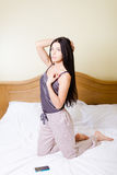 Sexy woman in pajamas kneeling on bed with phone Stock Images
