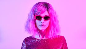 Glamour woman in fashion neon light. Party. Woman in party bright luxury outfit. High Fashion. Model girl with pink blonde dyed hair, makeup. Colorful neon light royalty free stock images